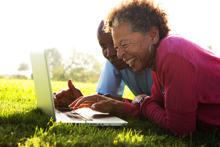 65 70: Senior couple lying in park using laptop