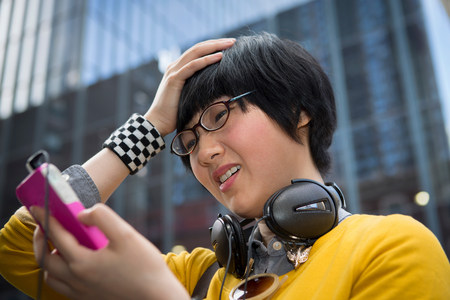 Young woman using mp3 player with hands in hair