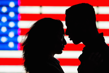 two persons only: Silhouette of young couple in front of American flag