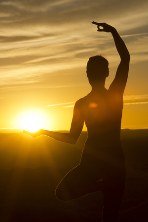 Young woman doing yoga in sunlight,Moab,Utah,USA