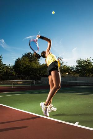 exerting: Female tennis player hitting ball