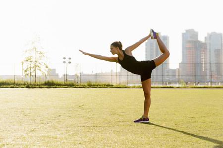 buen vivir: Hembra joven haciendo estiramiento de yoga en el parque de la ciudad