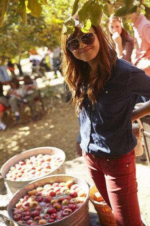 Young woman standing beside barrels of apples LANG_EVOIMAGES