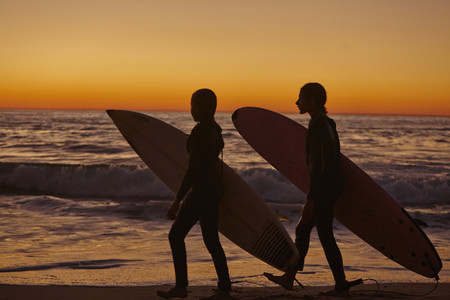 Two girls walking along beach at sunset carrying surfboards LANG_EVOIMAGES
