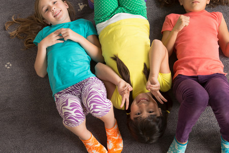 Three girls lying on floor wearing bright clothes LANG_EVOIMAGES