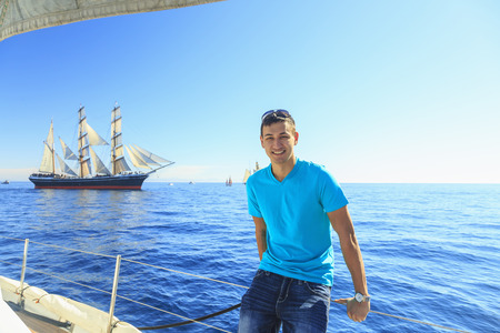 fenced in: Young man sailing, San Diego, California, USA