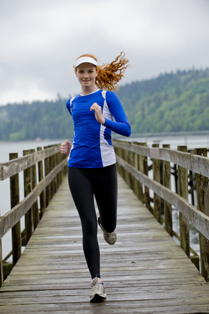 impulsive: Teenage girl running on pier,Bainbridge Island,Washington,USA