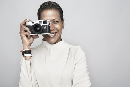 concealing: Studio portrait of happy mature woman holding up camera