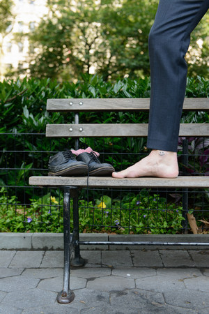 One leg and pair of shoes on bench