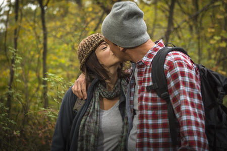 Mature couple kissing in forest LANG_EVOIMAGES