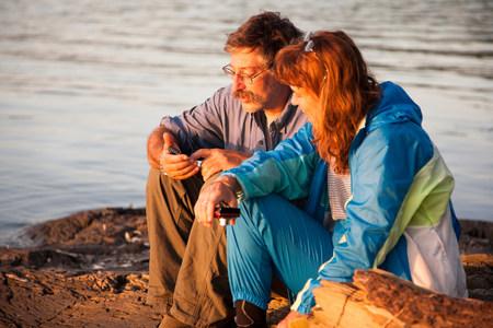 Mature couple sitting lakeside with mobile phones,Bath,Maine,USA