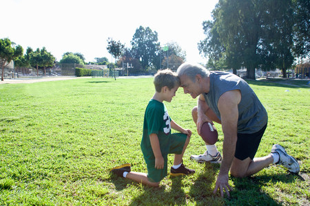 Boy and grandfather head to head,man holding football LANG_EVOIMAGES