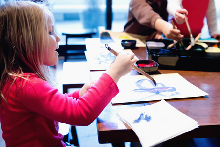 Three young siblings painting pictures at table LANG_EVOIMAGES