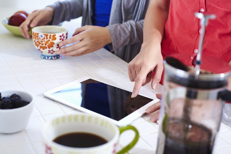 two persons only: Two young women in kitchen using digital tablet whilst having coffee