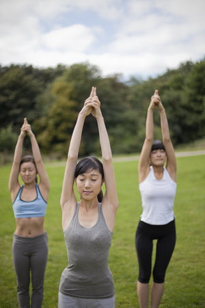Three young women in park practicing yoga position