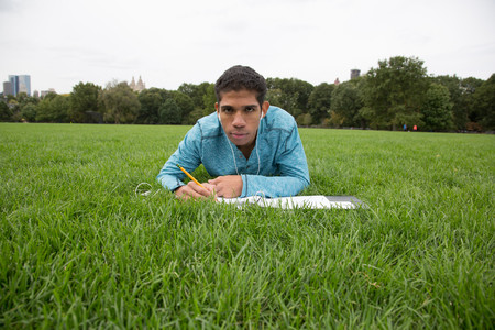 Young man lying on grass doing homework