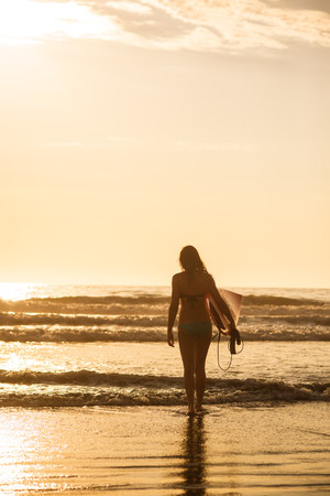 sunrises: Young woman with surfboard at sunset,La Jolla,San Diego,California,USA