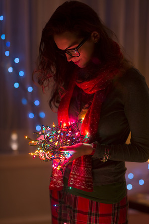 tangling: Young woman holding tangle of christmas lights LANG_EVOIMAGES