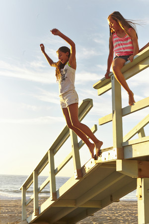 impulsive: Two girls playing at beach, jumping off boardwalk