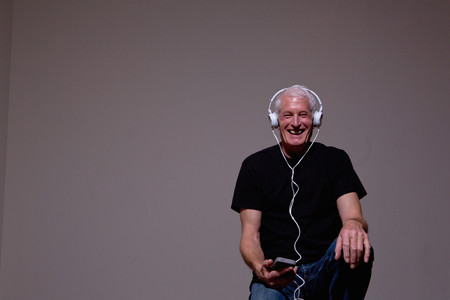 electronic music: Portrait of senior man listening to MP3 player on headphones