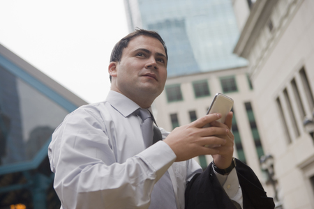 Businessman in city surrounded by skyscrapers