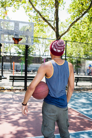 Young man looking towards basketball hoop on court