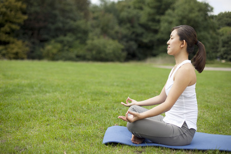 Young woman in park practicing yoga lotus position