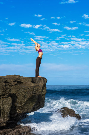 energy work: Woman doing yoga at coast LANG_EVOIMAGES