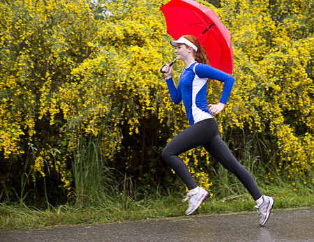 energy work: Teenage girl jogging with umbrella on road,Bainbridge Island,Washington,USA LANG_EVOIMAGES