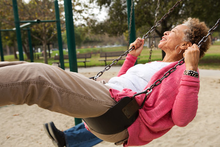 two persons only: Senior woman on swing in park