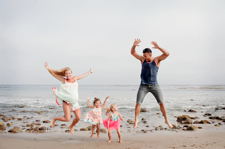 Parents and two young girls jumping mid air on beach