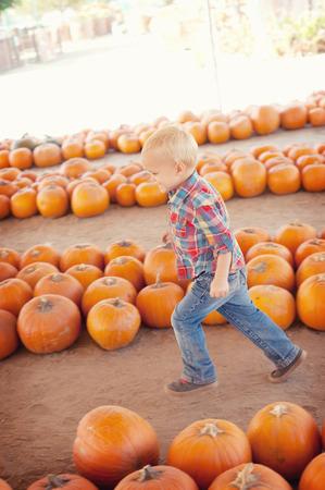 Boy running through pumpkins LANG_EVOIMAGES