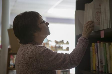 shop keeper: Health food store owner arranging books
