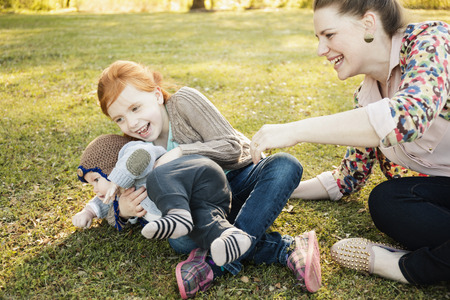 5.0: Mid adult mother, daughter and baby son on grass in park LANG_EVOIMAGES