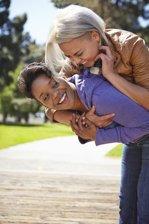 complicity: Lesbian couple having fun on piggy back in park