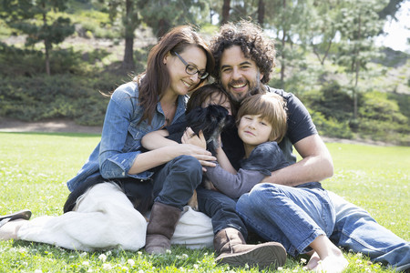 Portrait of family with two boys and dog sitting in park LANG_EVOIMAGES
