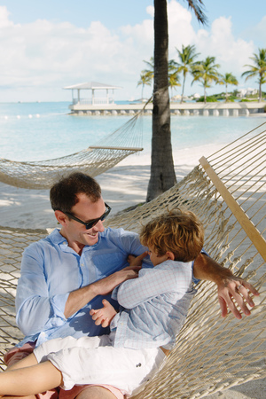 seaboard: Father and son relaxing in beach hammock, Providenciales, Turks and Caicos Islands, Caribbean