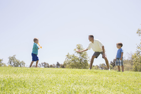 Father and sons playing baseball at park