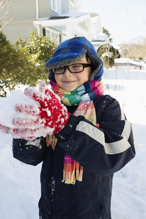 wintry weather: Boy making snowball, smiling LANG_EVOIMAGES