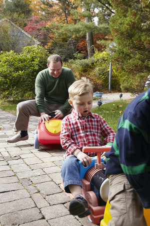Father and young sons playing on toy cars in garden