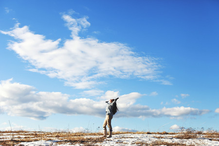 Mature woman with arms outstretched in landscape