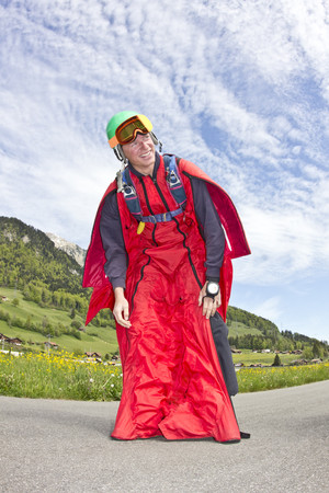 tiredness: Happy and relieved young man after landing in wingsuit