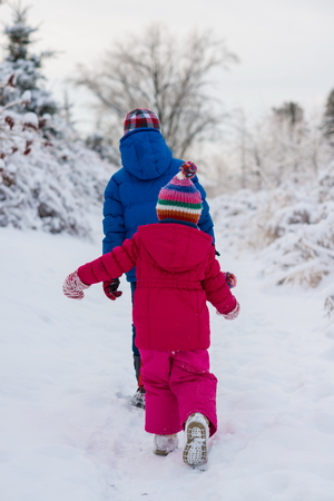 Brother and sister walking in snow LANG_EVOIMAGES