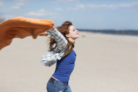 Young woman holding up blanket on windy beach LANG_EVOIMAGES