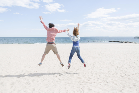 Rear view of couple jumping mid air on beach LANG_EVOIMAGES