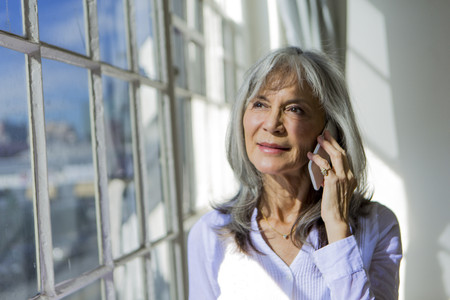 65 69 years: Senior woman looking out of window whilst using smartphone