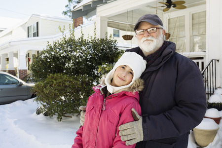 age 10 12 years: Grandfather and granddaughter outside house in winter