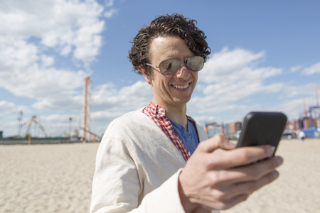 Mid adult man texting on smartphone at beach