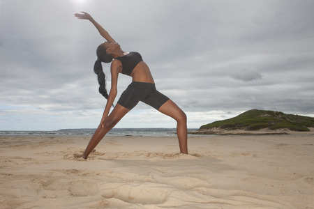Young woman practicing yoga position on beach