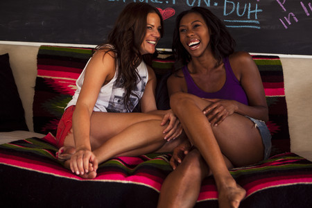 two persons only: Two young women sitting on sofa laughing LANG_EVOIMAGES